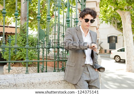European businessman waiting in a classic city street and checking the time in his watch during a sunny day, outdoors. - stock photo