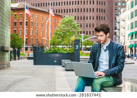 European businessman working on street in New York. Wearing leather jacket, jeans, young guy with beard, sitting on marble bench, reading, working on laptop computer. American flags on background.