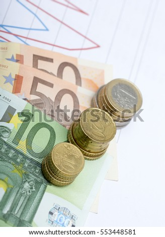 European cash. Coins and bank notes of 50 and 100. Also a chart of stock exchange rates or sales are in the background.