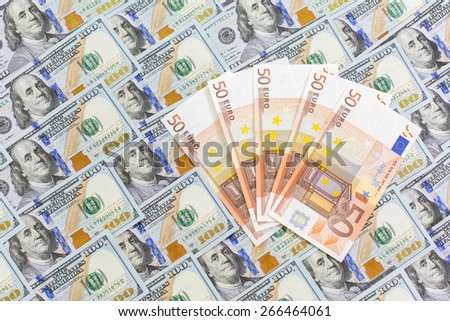 European cash notes over the layer of US dollars. The desk covered with US dollars hundreds new notes and several fifty Euro notes - stock photo