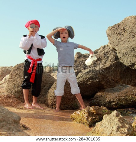 European children smiling boy and girl in fancy dress pirate looking for buried treasure on the sea coast in summer - stock photo