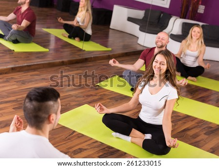 european coach showing to adult learners new yoga posture at class - stock photo