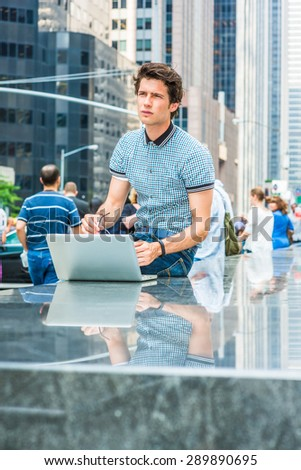 European college student study in New York. Wearing blue pattered shirt, holding glasses, a young handsome guy working on laptop computer on street, looking up, thinking. Many people on background. - stock photo