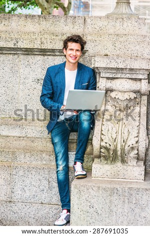 European college student studying in New York. Wearing blue blazer, jeans, sneakers, a young guy staying at quiet corner on campus, working on laptop computer, reading, thinking. Working Outside.  - stock photo