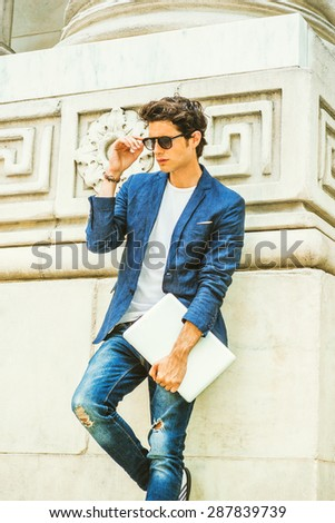 European college student studying in New York. Wearing blue blazer, jeans, sunglasses, holding laptop computer, a young guy standing by column on campus, looking down, thinking. Instagram effect. - stock photo