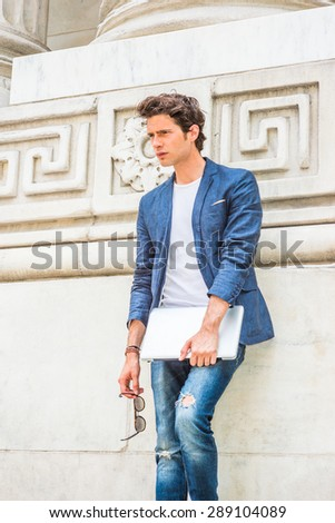European college student studying in New York. Wearing blue blazer, white under shirt, jeans, holding laptop computer, sunglasses, a young guy standing by column on campus, relaxing. thinking.  - stock photo