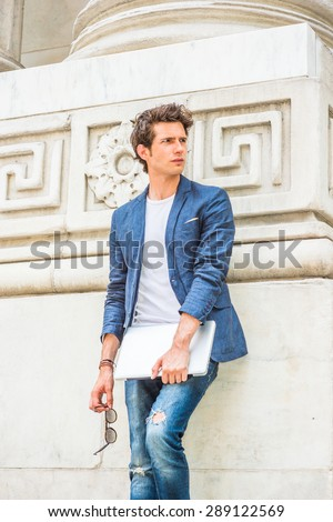 European college student studying in New York. Wearing blue blazer, white under shirt, jeans, holding laptop computer, sunglasses, a young guy standing by column on campus, looking away, relaxing. - stock photo