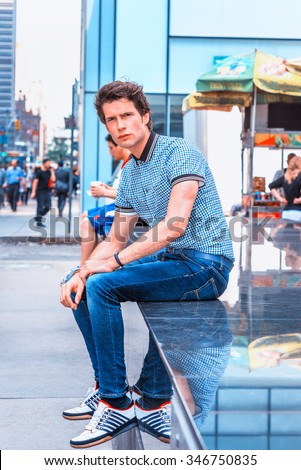 European college student traveling in New York. Wearing blue pattered short sleeve shirt, jeans, sneakers, a guy sitting on stage on street with high buildings, thinking. Photo stylized look.  - stock photo