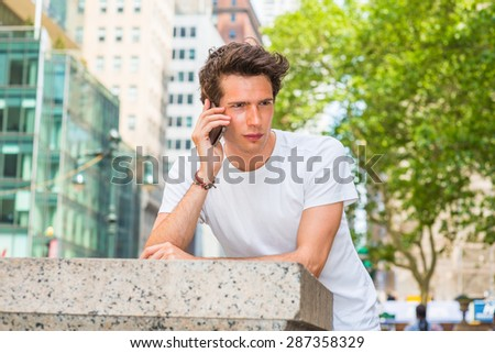 European college student traveling in New York. Wearing white T shirt, a young guy looking down, thinking, calling on his mobile phone outside on street in summer. Technology in our daily life. - stock photo