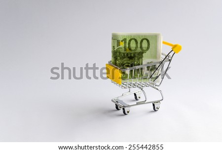 European currency. Hundred Euro in shopping trolleys on a white background. - stock photo