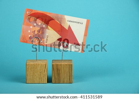 European economy crisis, decline of Euro currency, ten Euro banknote with red arrow down at wooden metal holders over blue background - stock photo