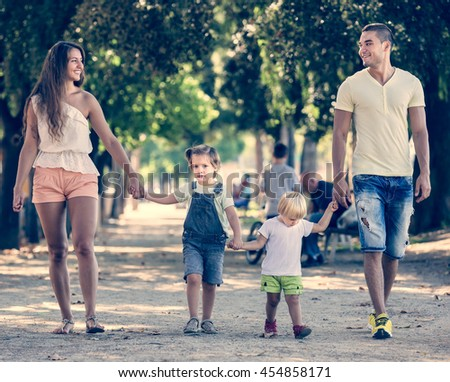European family with two little children walking in park on sunny day