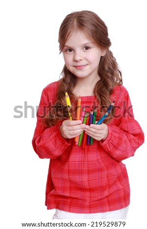 European first grader holding colorful pencils on white background - stock photo