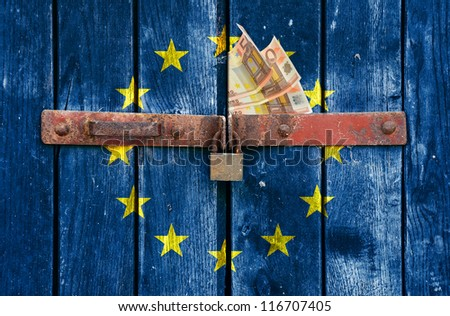 European flag with the Euro money on the background of old locked doors - stock photo