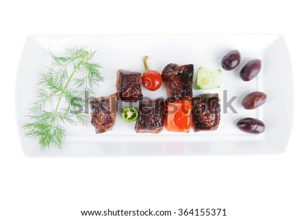 european food: grilled beef meat on white china plate isolated on white background with olives and tomatoes - stock photo