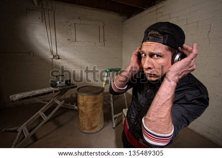 European hip hop guy with backwards cap and earphones - stock photo