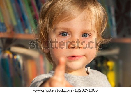 European kid with blond hair on the background of bookshelves