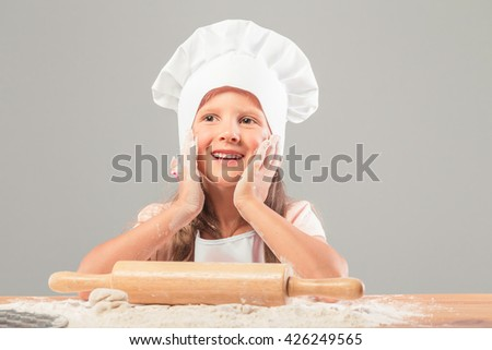 European little girl in chef hat and in pinafore knead the dough from flour. On the table is scattered flour and a rolling pin is for test.