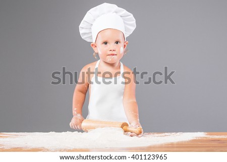 European little girl in chef hat and in pinafore rolls the dough. Shooting in the studio on a gray background. - stock photo