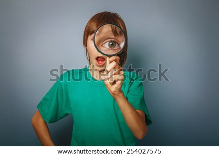 European-looking boy of ten years a joke, looking through a magnifying glass, large eyes, open mouth on a gray background cross process