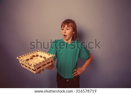 European-looking  boy of  ten years  holding an empty basket in hand on gray background retro
