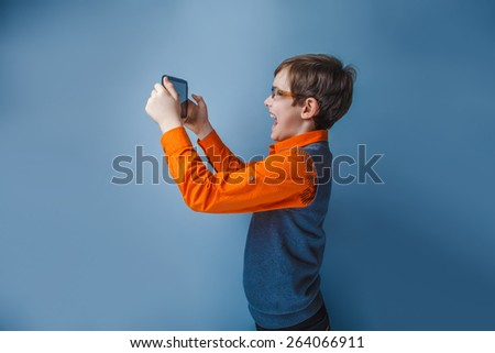 European-looking boy  of ten  years in  glasses holding tablet in hand, plays on a blue background