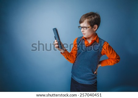 European-looking boy of  ten years in glasses  looks at the plate on a gray background