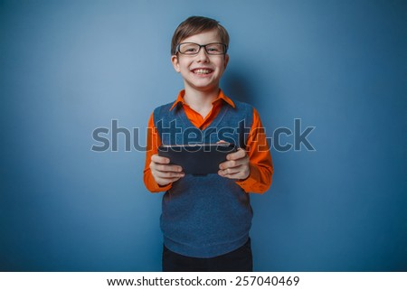 European-looking boy of ten years in glasses plays in tablet, smiling on a gray background - stock photo