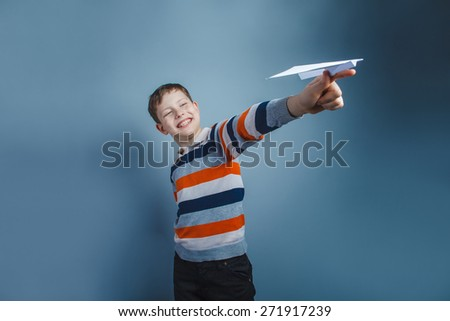 European-looking boy of ten years playing paper airplane on a gray background - stock photo