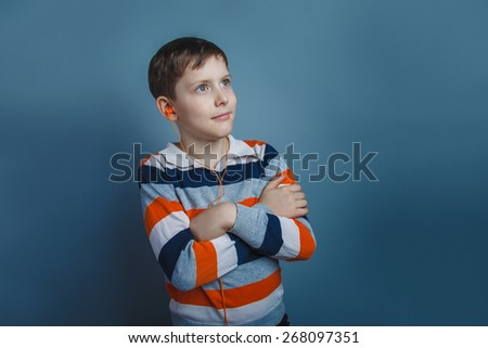 European-looking boy  of ten years with  headphones  listening to music on a gray background - stock photo