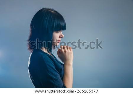 European-looking girl brunette in black jacket folded her hands in prayer on a gray background, faith, prayer - stock photo