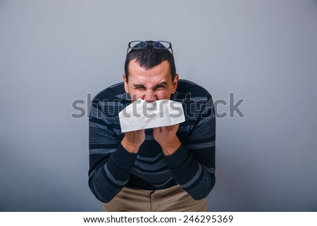 European-looking male of about thirty brunet blowing his nose into a handkerchief on a gray background, runny nose - stock photo