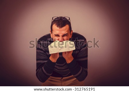 European-looking male of about thirty brunet blowing his nose into a handkerchief on a gray background, runny nose cross process retro - stock photo