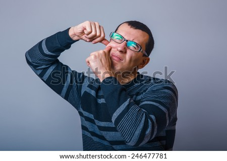 European-looking male of about thirty brunet squeezing a pimple on the face - stock photo