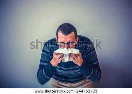 European-looking man of 30 years is sick, cold, handkerchief cross process - stock photo