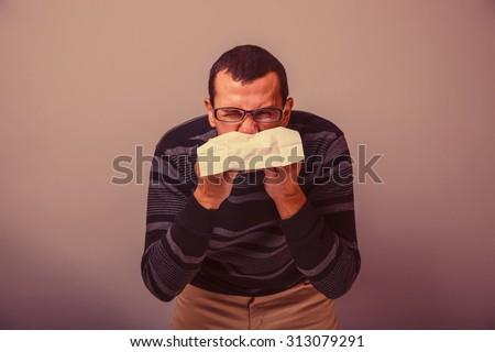 European-looking man of 30 years is  sick,  cold,  handkerchief retro - stock photo
