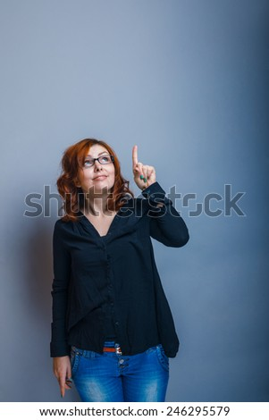 European-looking woman of about thirty redhead shows his hand up on a gray background - stock photo