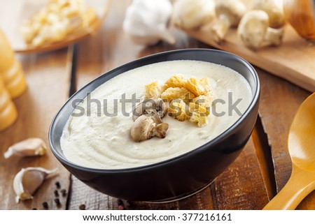 European lunch cooking, cream soup made of mushrooms on wooden table, delicious food