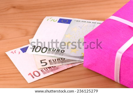 european money and red box on wooden plate - stock photo