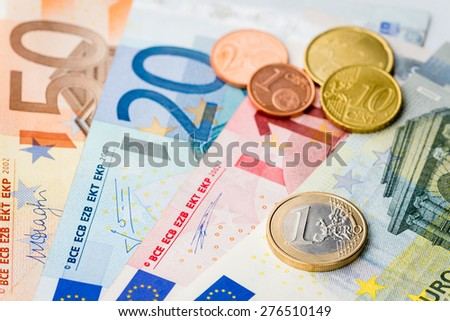 European money - one Euro coin with Euro cents and banknotes in the background - stock photo