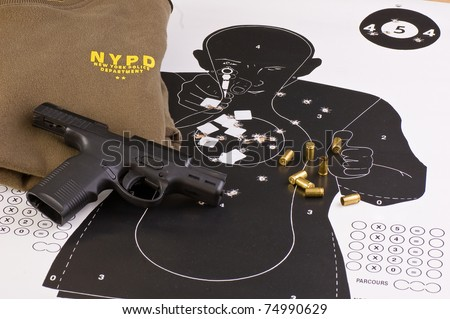 European Police Target with holes, 9mm pistol, shell casings and sweater - stock photo