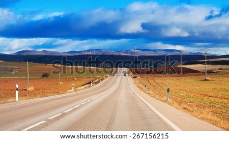 European road among fields and hills under  cloudy sky - stock photo