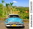 European senior couple having fun touring around Vinales valley, Cuba, in an vintage old-timer car - stock photo