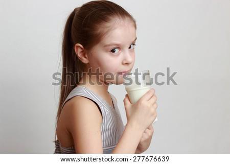 European smiley little girl holding white cow milk in glass - stock photo