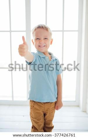 European smiling boy in blue shirt making thumbs up - stock photo