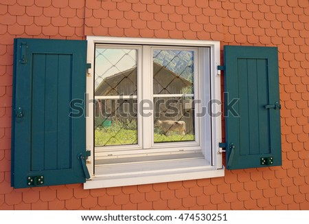 European style house window with green shutters and reflection of country barn and cow