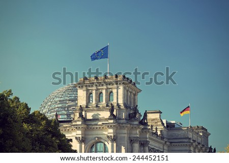 European Union (EU) and German flag on the national German parliament (Reichstag building), vintage style - stock photo
