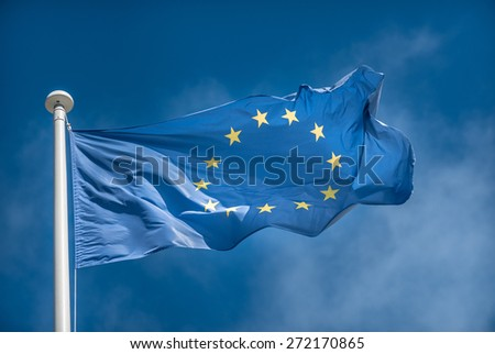 European Union flag blowing in the wind on blue sky background