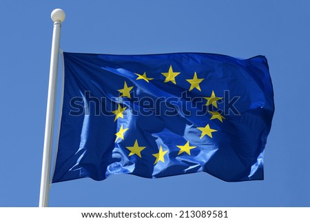 European Union flag flying from a flagpole fluttering in the breeze against a blue sky