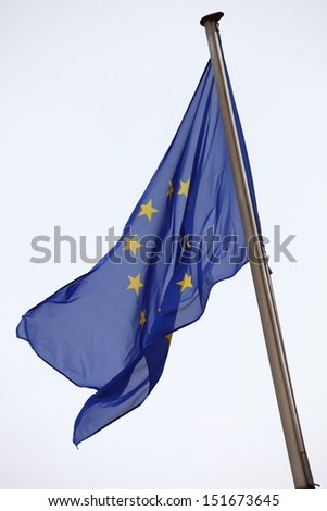 European Union flag flying on a flagpole against a light grey sky with copyspace